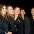 vijf lachende vrouwen tijdens een fotoshoot